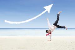 Affärsmandansen och förhöjningpiltecknet fördunklar på stranden Arkivbild