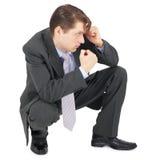 affärsmandefensiv poserar att sitta Arkivfoto