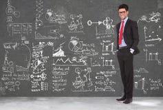 Affärsmanen står framme av blackboarden royaltyfria foton