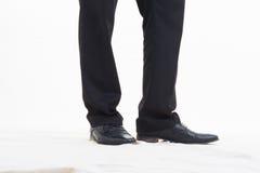 Affärsmanfot i svartskor på vit bakgrund Fotografering för Bildbyråer