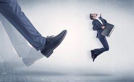 Affärsmanfot som sparkar småföretagaren arkivfoton
