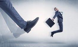 Affärsmanfot som sparkar småföretagaren royaltyfri fotografi