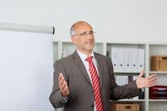 AffärsmanGesturing While Giving presentation i regeringsställning royaltyfria bilder
