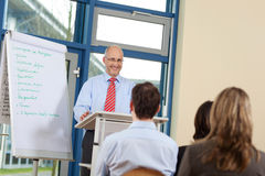 AffärsmanGiving Presentation To Coworkers, medan stå på P fotografering för bildbyråer