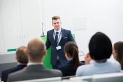 AffärsmanGiving Presentation To kollegor i hörsal fotografering för bildbyråer
