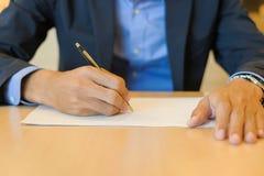 Affärsmanhänder som undertecknar på dokument royaltyfri foto