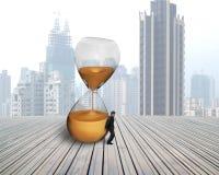 Affärsmanhåll det benägna timglaset Fotografering för Bildbyråer