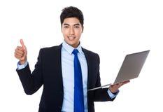 Affärsmanhåll med den bärbar datordatoren och tummen upp Fotografering för Bildbyråer