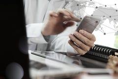 Affärsmanhand genom att använda bärbara datorn och mobiltelefonen för tom skärm Arkivbild