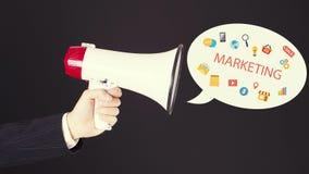 Affärsmanhand med högtalaren med symboler som ut flyger Marknadsföringsstrategier Arkivbilder