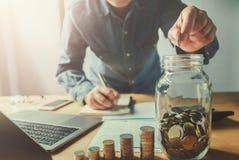 affärsmanhand som sätter mynt in i tillbringareexponeringsglas Sparande pengarconce arkivfoton