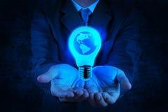Affärsmanhanden visar den ljusa kulan med planetjord Arkivbild