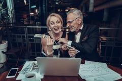 Affärsmanhandlagkvinna och att ge pengar till henne fotografering för bildbyråer