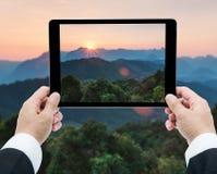 Affärsmanhandminnestavla som tar bilder majestätisk solnedgång i Royaltyfria Bilder