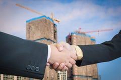 Affärsmanhandskakning med byggnadskonstruktion Arkivfoton