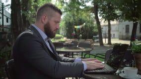 Affärsmanhandstil på bärbara datorn som är utomhus- steadicamskott arkivfilmer