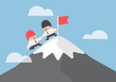 Affärsmanhjälp hans vän till att nå överkanten av berget Royaltyfria Foton