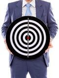 Affärsmaninnehav en dartboard royaltyfria bilder