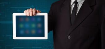 Affärsmaninnehav en modern tablet för vit med oskarpa apps royaltyfria bilder