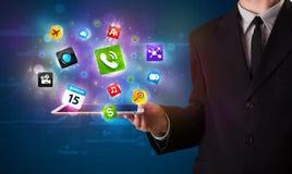Affärsmaninnehav en tablet med moderna färgrika apps och symboler Royaltyfri Bild