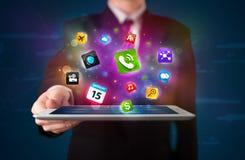 Affärsmaninnehav en tablet med moderna färgrika apps och symboler Arkivfoton