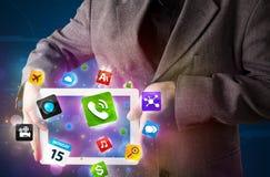 Affärsmaninnehav en tablet med moderna färgrika apps och symboler Arkivfoto