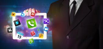 Affärsmaninnehav en tablet med moderna färgrika apps och symboler Royaltyfria Bilder