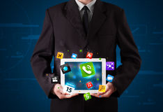 Affärsmaninnehav en tablet med moderna färgrika apps och symboler Arkivbild