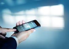 Affärsmaninnehav och visning en smartphone med stockmarketbloggen på skärmen, tom text Royaltyfria Bilder