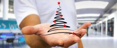 Affärsmaninnehavet och rörande julträd skissar Fotografering för Bildbyråer