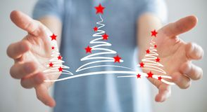 Affärsmaninnehavet och rörande julträd skissar Arkivbild