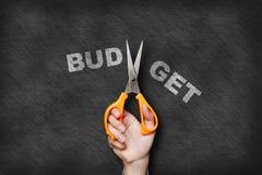 Affärsmaninnehavet scissor budget- text för klipp på svart tavla Fotografering för Bildbyråer