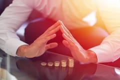 Affärsmaninnehavhänder över växande myntkolonner Royaltyfri Foto