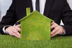 Affärsmaninnehavhus av gräs Arkivfoto