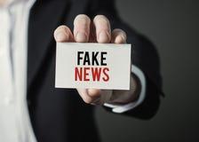 Affärsmaninnehavpapper med text fejkar nyheterna Arkivbild