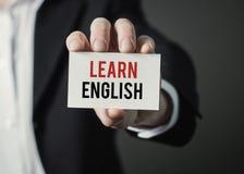 Affärsmaninnehavpapper med text lär engelska Arkivfoto