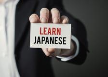 Affärsmaninnehavpapper med text lär japan Royaltyfria Bilder