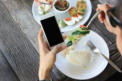 Affärsmaninnehavsmartphone och halunch i restaurang royaltyfria bilder