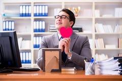 Affärsmankänslaförälskelsen och älskat i kontoret royaltyfri foto