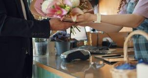 Affärsmanköpandeblommor som direktanslutet betalar med smartphonen i blomsterhandlare, shoppar arkivfilmer