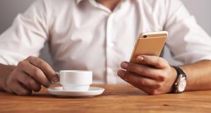 Affärsmankaffesmartphone arkivfoton