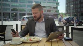 Affärsmankopieringsdata från minnestavlan till smartphonen, under lunch, steadicam lager videofilmer