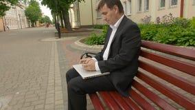 Affärsmankvittrande på mobiltelefonsammanträde på en bänk i gata stock video