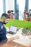 Affärsmanläsebok, medan genom att använda bärbara datorn i regeringsställning arkivfoto