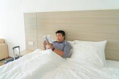 Affärsmanläsebok på säng för avkoppling arkivbild