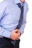Affärsmanlidande från magen smärtar. Arkivfoto