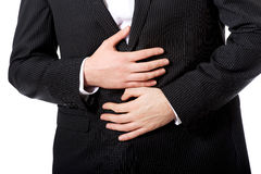 Affärsmanlidande från magen smärtar Arkivbilder