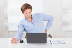 Affärsmanlidande från ryggvärk, medan arbeta på bärbara datorn Royaltyfri Bild