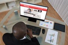 AffärsmanLooking At Business nyheterna på datoren Royaltyfria Foton