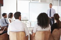 AffärsmanMaking Presentation To kollegor i regeringsställning arkivfoto